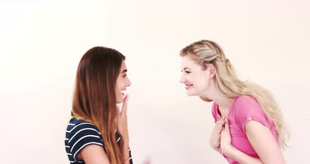 contar : Blonde telling secret to brunette friend on white screen