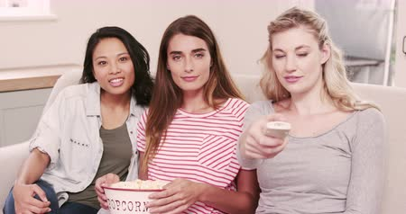 pipoca : Female friends watching a movie on the couch at home Stock Footage