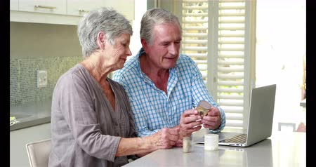discussão : Senior couple using laptop and holding pills together