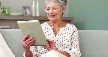 таблетка : Senior woman using tablet on couch Стоковые видеозаписи
