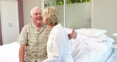 consolador : Senior couple talking together on bed