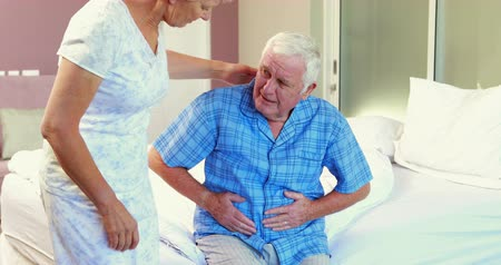 gyomor : Suffering senior man holding his belly on bed