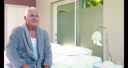 sufferance : Suffering senior man holding his belly on bed