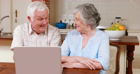 home life : Senior couple using laptop together at home Stock Footage