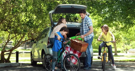otopark : Family unloading car trunk on a sunny day Stok Video