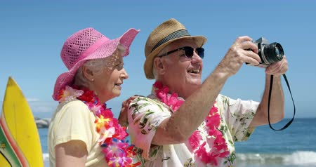 vacation : Senior couple taking picture on the beach Stock Footage