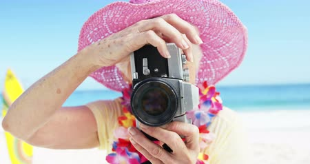 fotografando : Senior woman taking picture on the beach