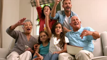 assistindo : Multi generation family on the sofa cheering while watching television in slow motion