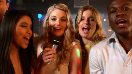 śpiew : Happy friends singing at the karaoke in night club in slow motion Wideo