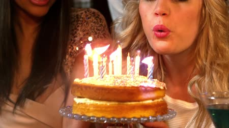 foukání : Happy friends celebrating birthday with cake in the night club in slow motion