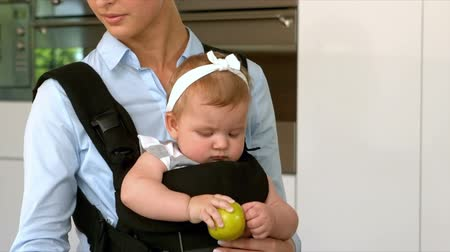 apple computers : Mother on laptop while holding daughter in kitchen Stock Footage