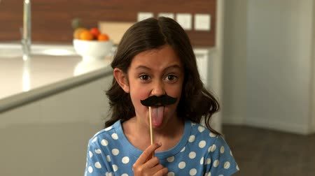 bigodes : Daughter with fake mustaches making faces in kitchen