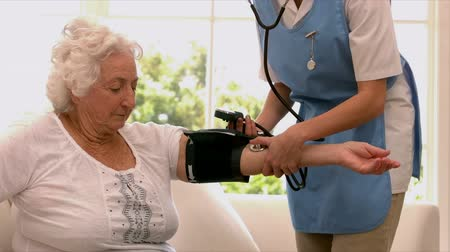 home life : Nurse taking blood pressure of senior woman at home