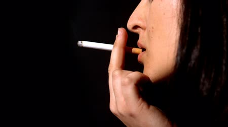 fumegante : Woman smocking a cigarette in slow motion on black background Stock Footage