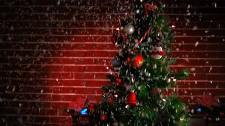 nevando : View of a decorated christmas tree while snowing in front of a brick wall Vídeos