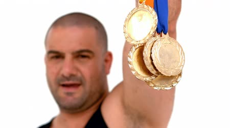 atleta : Happy athlete holding medals on white screen Stock Footage