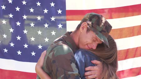 soldados : Handsome soldier reunited with partner against an american flag Stock Footage