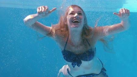 sualtı : Pretty woman showing a thumbs up underwater in the pool Stok Video