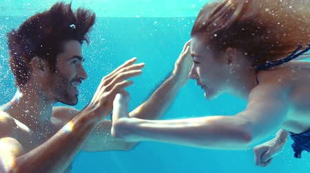 sualtı : Happy couple cheering underwater in the pool Stok Video