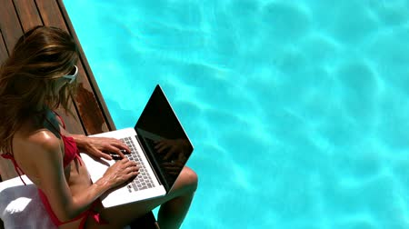 tonları : Attractive brunette resting and using laptop poolside