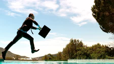 oblek : Businessman jumping in the swimming pool with his briefcase Dostupné videozáznamy