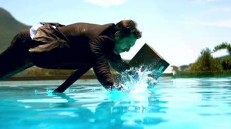 suit and tie : Businessman jumping in the swimming pool in slow motion