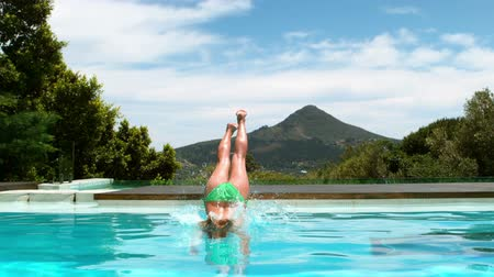 basen : Attractive woman diving into swimming pool on his holidays