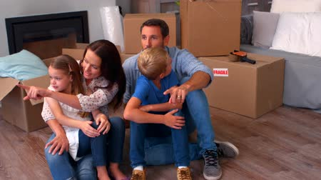 dom : Family relaxing while moving house sitting on the floor Wideo