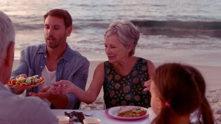 comer : Happy extended family eating on the beach Vídeos