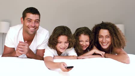 assistindo : Cute family watching tv and changing channels lying on their bed in slow motion Vídeos
