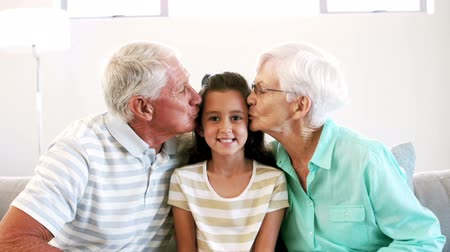 внучка : Grandparents kissing their granddaughter in the living room