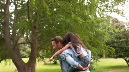parque : Handsome father giving piggy back to his daughter in a park in slow motion