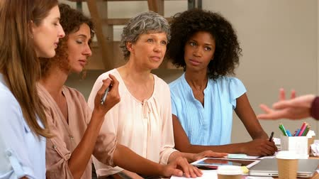 sheet : Woman presenting information in front of other women