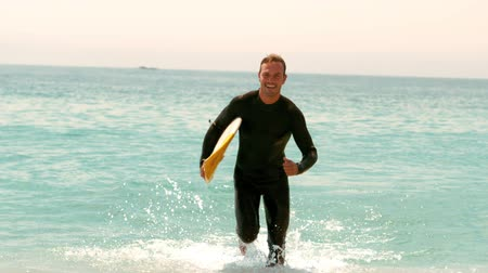 surf : Man with surfboard running out of the water Dostupné videozáznamy