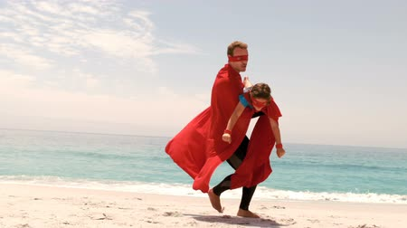 kahraman : Father and son dressed as superhero on the beach