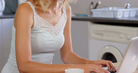 pizsama : Cute blonde using laptop in kitchen in slow motion Stock mozgókép