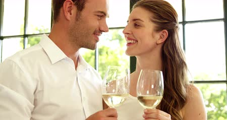kutluyor : Couple toasting with white wine in restaurant in slow motion