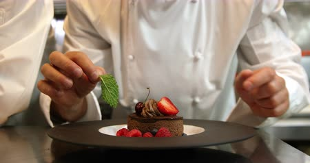 acabamento : Chefs putting finishing touch on desserts in slow motion