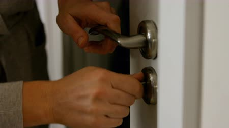 фронт : Woman closing the door with a key