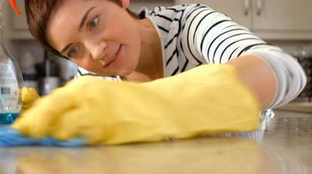 cleaning products : Woman cleaning counter in her kitchen Stock Footage