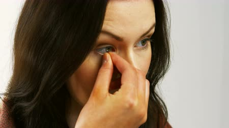 soczewki kontaktowe : Woman removing her contact lenses on white background