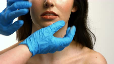 dokunaklı : Plastic surgeon touching woman face on white background Stok Video