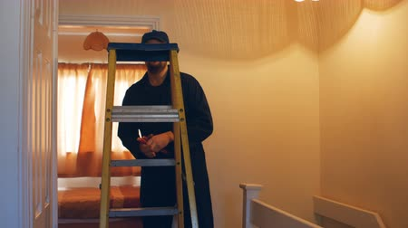 elektryk : Man fixing the fire detector with a ladder