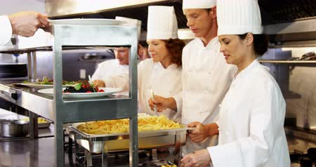 prepare food : Group of chefs giving plates on order line in a restaurant kitchen