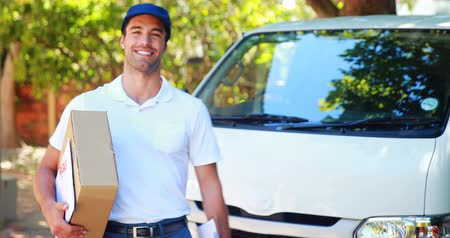 paket : Delivery man carrying a parcel in front of his van