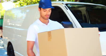 teslim : Delivery man carrying a parcel in front of his van