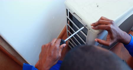 refrigerant : Repairman fixing air conditioning inside a house