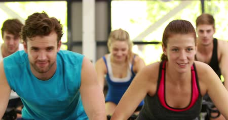sınıf : Fit group of people using exercise bike togetherat crossfit Stok Video