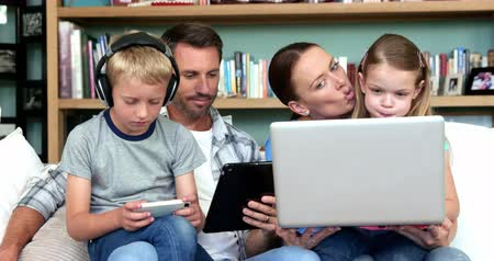 home life : Cute family using technologies sitting on the couch at home