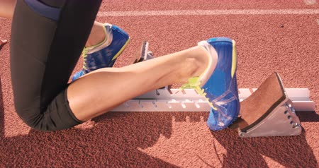 atlet : Athlete woman waiting in the starting block on running track Stok Video